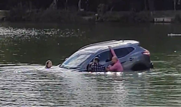 Heroic passers-by save trapped pensioner and dog after car plunged into lake