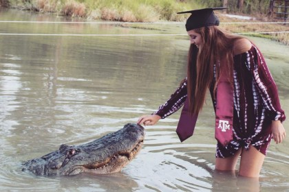 US student poses with alligator for graduation photos